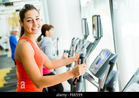 Young fit woman using an elliptic trainer in a fitness center and smiling - Stock Photo