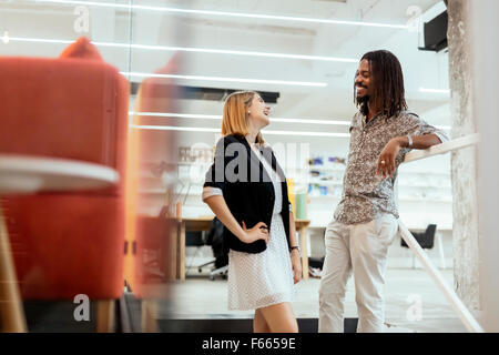 Colleagues talking on stairs in a modern office - Stock Photo