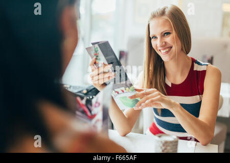Young friends in cafe gossiping before ordering - Stock Photo