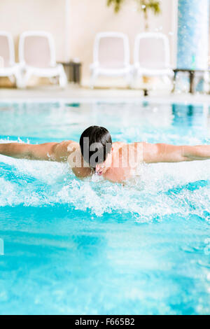 Swimming stroke of a handsome muscular fit male in a pool - Stock Photo