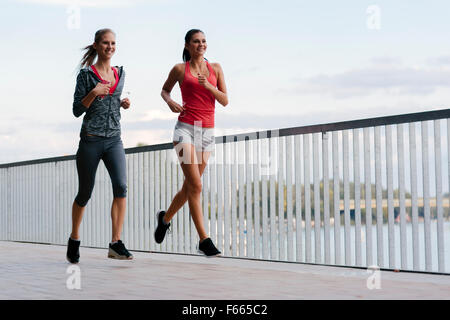 Two sporty women jogging in city while listening to music - Stock Photo