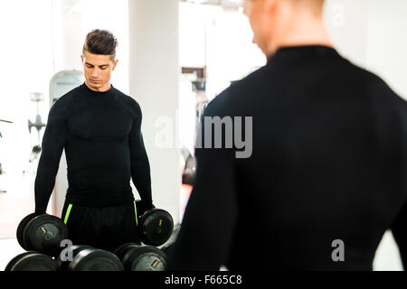 Young muscular man working out in a gym and lifting weights with his reflection showing in a mirror - Stock Photo