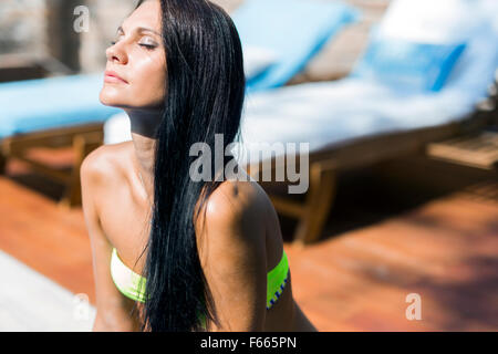 Beautiful woman with closed eyes sunbathing at the poolside - Stock Photo