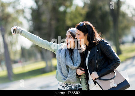 Two young women taking a selfie of themselves on a sunny day - Stock Photo