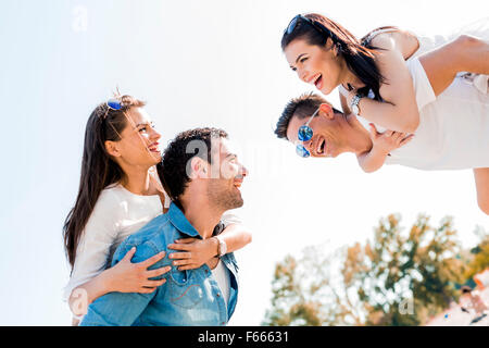 Group of young happy people carrying women on a sandy beach piggyback - Stock Photo