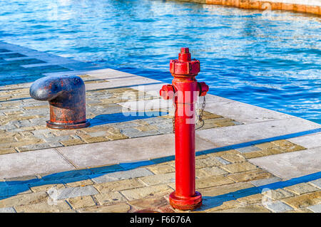 bollard and red fire hydrant on the quay - Stock Photo