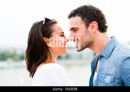 Young beautiful couple rubbing noses as a sign of love and about to kiss each other