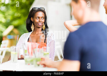 Young and happy friends sitting talking at a table outdoors and smiling