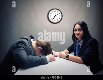 Tired man asleep during talks in the office - Stock Photo