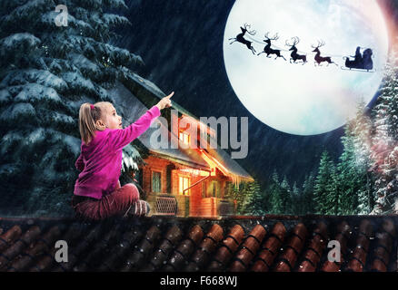 Girl sits on the roof in The Christmas eve pointing to the deer in the sky - Stock Photo