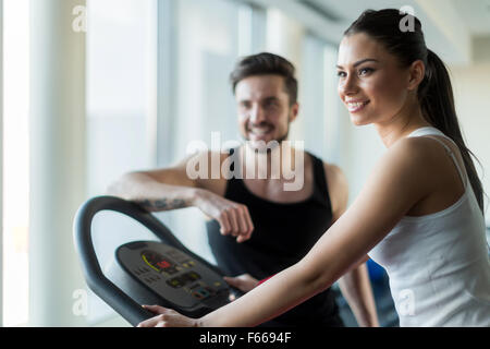 Beautiful, young people talking in a gym while working out and burning calories - Stock Photo