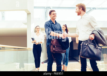 Businessmen shaking hands and greeting each other cheerfully - Stock Photo