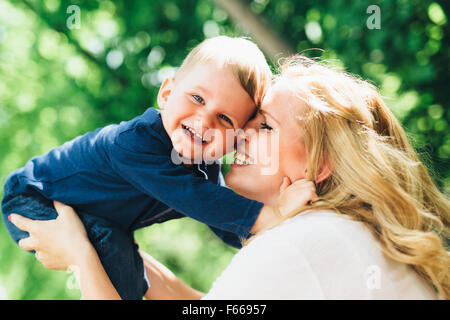 Mother smiling laughing and playing with her child outdoors on a nice summer day - Stock Photo