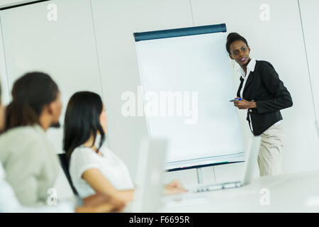 Young business people sitting at a conference table while listening to their  colleague and learning new technologies - Stock Photo