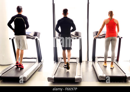 Group of young people using treadmills in a fitness center - Stock Photo