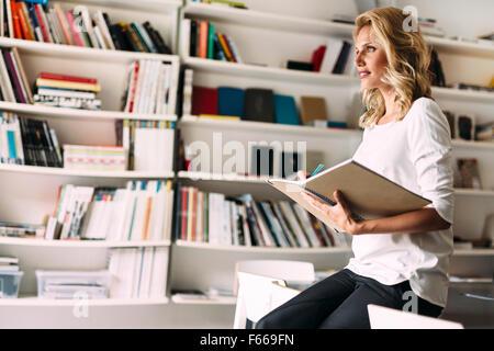 Stunning blonde woman reading - Stock Photo