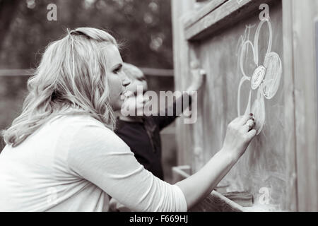 Beautiful mother and son drawing on blackboard with chalk - Stock Photo