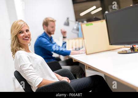 Beautiful blonde sitting in an office and working - Stock Photo