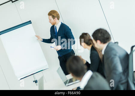 Young business people sitting at a conference table while listening to the lecturer  and learning new technologies - Stock Photo