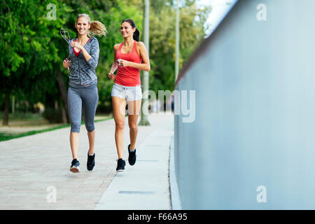 Two women exercising by jogging in city - Stock Photo