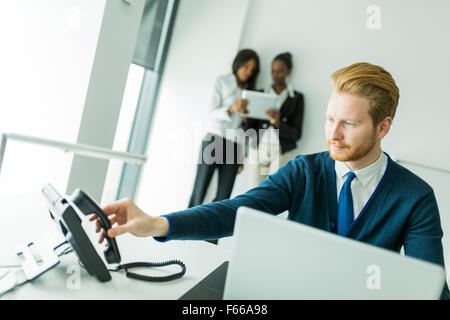 Businessman about to answer the phone with two beautiful,  young women having a conversation in the background - Stock Photo