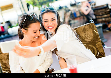 Two young beautiful women taking a selfie of themselves during lunch break - Stock Photo