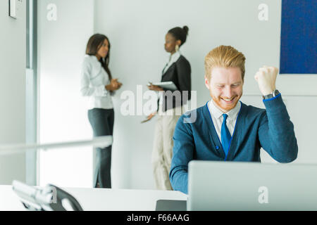 Successful businessman being happy for achieving his goals as he sees good news on the laptop - Stock Photo