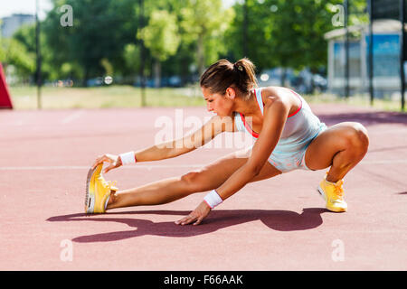 Beautiful young athletic woman stretching in summer before running - Stock Photo