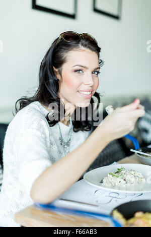 Beautiful young lady having a meal in a restaurant and about to take a bite - Stock Photo