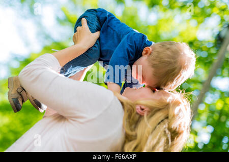 Beautiful young mother playing and smiling with her handsome little son - Stock Photo