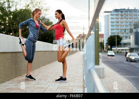 Two women stretching feet before jogging - Stock Photo