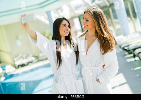 Two beautiful girls  taking a selfie next to a swimming pool - Stock Photo