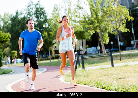 A man and a woman jogging on a city track - Stock Photo