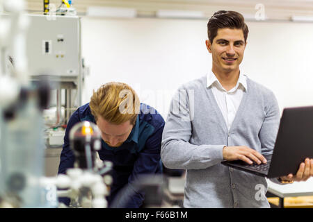 Portrait of ayoung handsome engineer checking data on a laptop and smiling - Stock Photo
