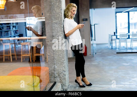 Beautiful blonde woman texting on cell phone - Stock Photo