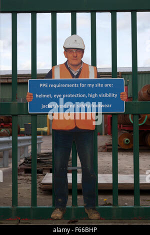 PPE requirements are helmet, eye protection, high visibility jacket/vest and safety footwear sign. Burscough, Lancashire, - Stock Photo