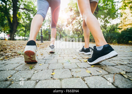 Closeup of female feet while jogging in nature outdoors in park - Stock Photo