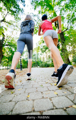 Women jogging in park and living a healthy sporty life - Stock Photo