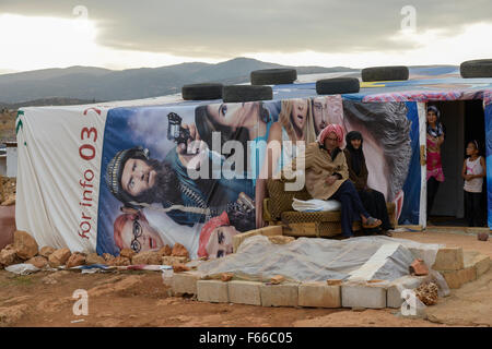 LEBANON Beqaa valley, Deir el Ahmad, camp for syrian refugees, family in tent made from old cinema poster / LIBANON - Stock Photo