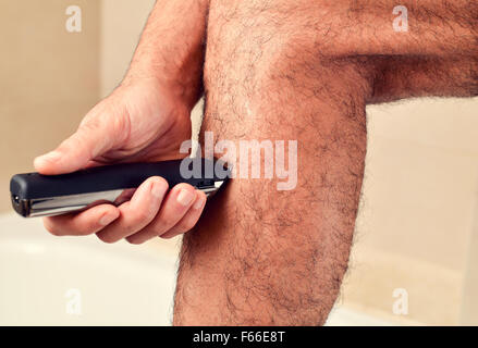 closeup of a young caucasian man trimming the hair of his legs with an electric trimmer - Stock Photo