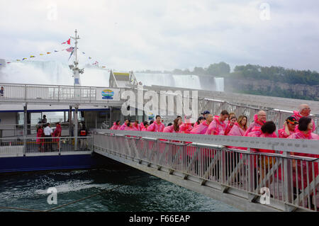 Tourists in ponchos exit the Hornblower boat after a Niagara Falls boat tour at the world famous Waterfall in Ontario. - Stock Photo