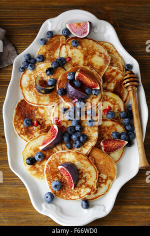 pancakes with berries and honey, top view - Stock Photo