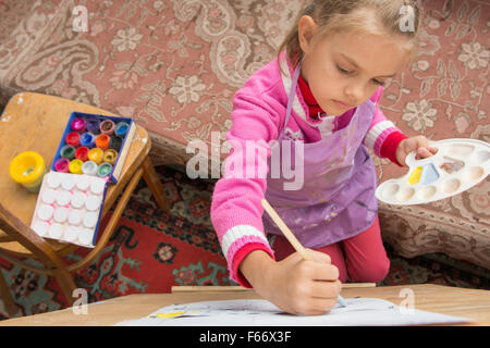 Five-year girl with a brush paints a picture on an easel and holding in his other hand in the artist's palette - Stock Photo