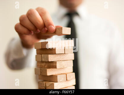 businessman builds a tower - Stock Photo