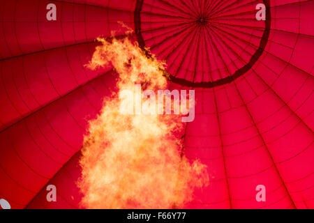 Gas flame heating hot air balloon to help it rise. - Stock Photo