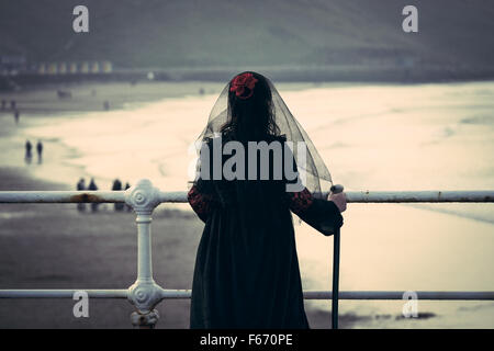 A young girl dressed in  Victorian mourning outfit for The Whitby Goth Weekend looks out over the beach and seafront. - Stock Photo