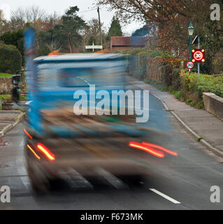 Speeding truck passing through a rural village, with the over 30mph warning sign flashing. - Stock Photo