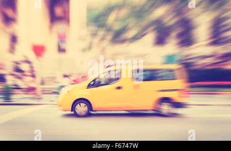 Vintage toned motion blurred yellow taxi on a street. - Stock Photo