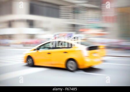 Motion blurred yellow taxi on a city street. - Stock Photo