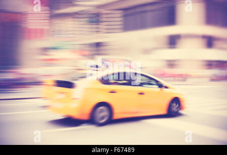 Vintage toned motion blurred taxi on street in New York, USA. - Stock Photo